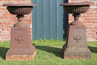Pair of Victorian cast iron planters classical urns on plinths