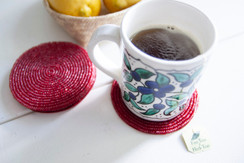 Rangeene Handmade Beaded Circle Red Coaster with a Coffee Mug on Top