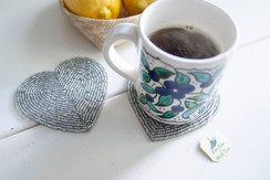 Rangeene Handmade Beaded Heart Siler Coaster with a Coffee Mug on Top