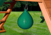 Green punching ball attached under a playset deck on a grass background.