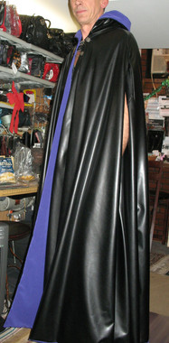 "Reversible Pleather and Peachskin Cape with Working Hood, button with chain closures in front, and armholes. Model is 6'4"" tall."