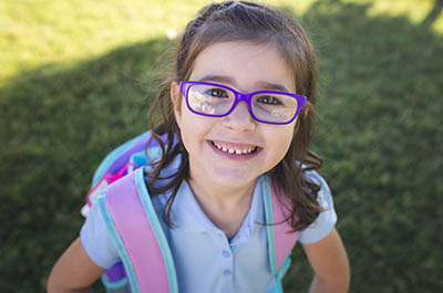 Little girl wearing her school uniform, backpack and purple glasses