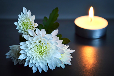 White chrysanthemums beside a lit candle