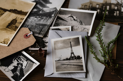 Vintage photos of the Eiffel Tower and other landmarks spread out on a table
