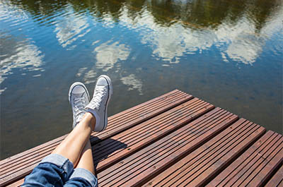The legs of a young woman, stretched out on a a pier, overlooking water that reflects the sky