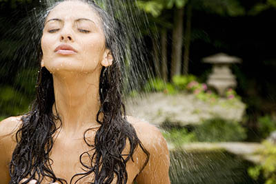 Young woman stands under an outdoor shower in a zen Japanese garden