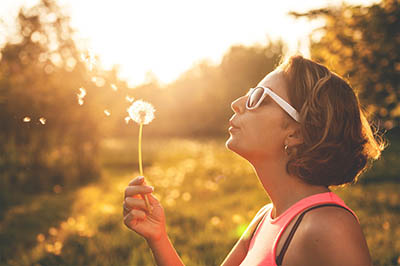 Young woman outdoors blowing on a dandelion and making a wish