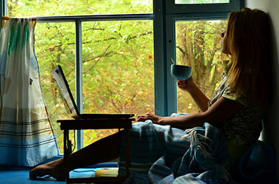 Woman at her laptop, drinking tea and procrastinating as she looks out the window