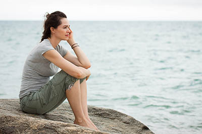 Woman sits on a rock, looking sadly out to sea