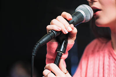 Young woman nervously grasps a microphone, about to speak or sing in public