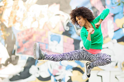 Strong, fierce young woman jumps and kicks the air in front of a graffiti wall