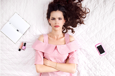 Cranky young woman wearing pink lies on her bed with her arms crossed