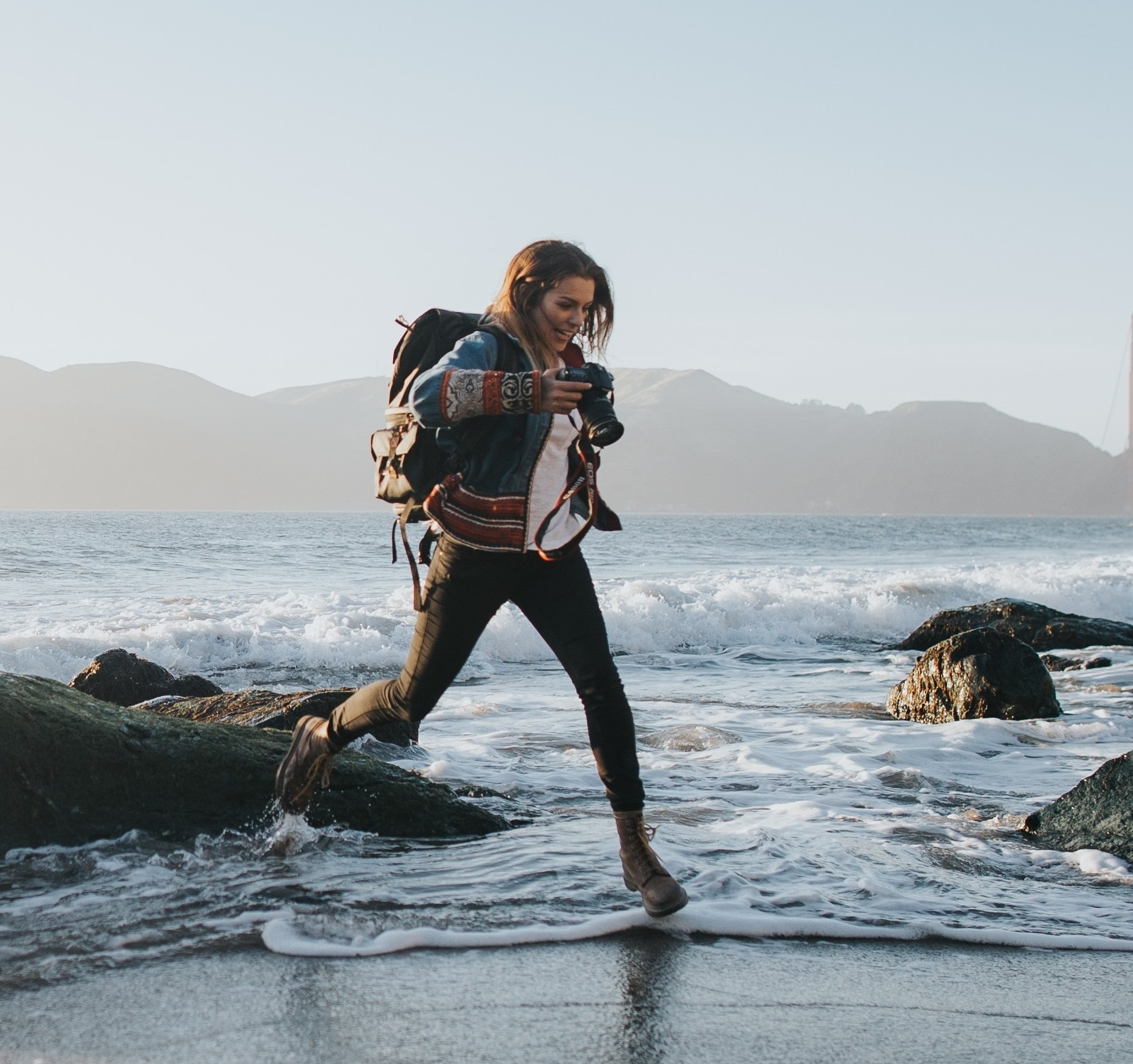 A young woman wearing a backpack and hiking gear smiles as she runs through water lapping at the shore