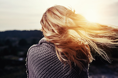 Woman wrapped in a shawl watches the sunrise as her blonde hair blows in the breeze