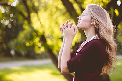 Woman outdoors with her eyes closed and hands clasped in prayer to the trees