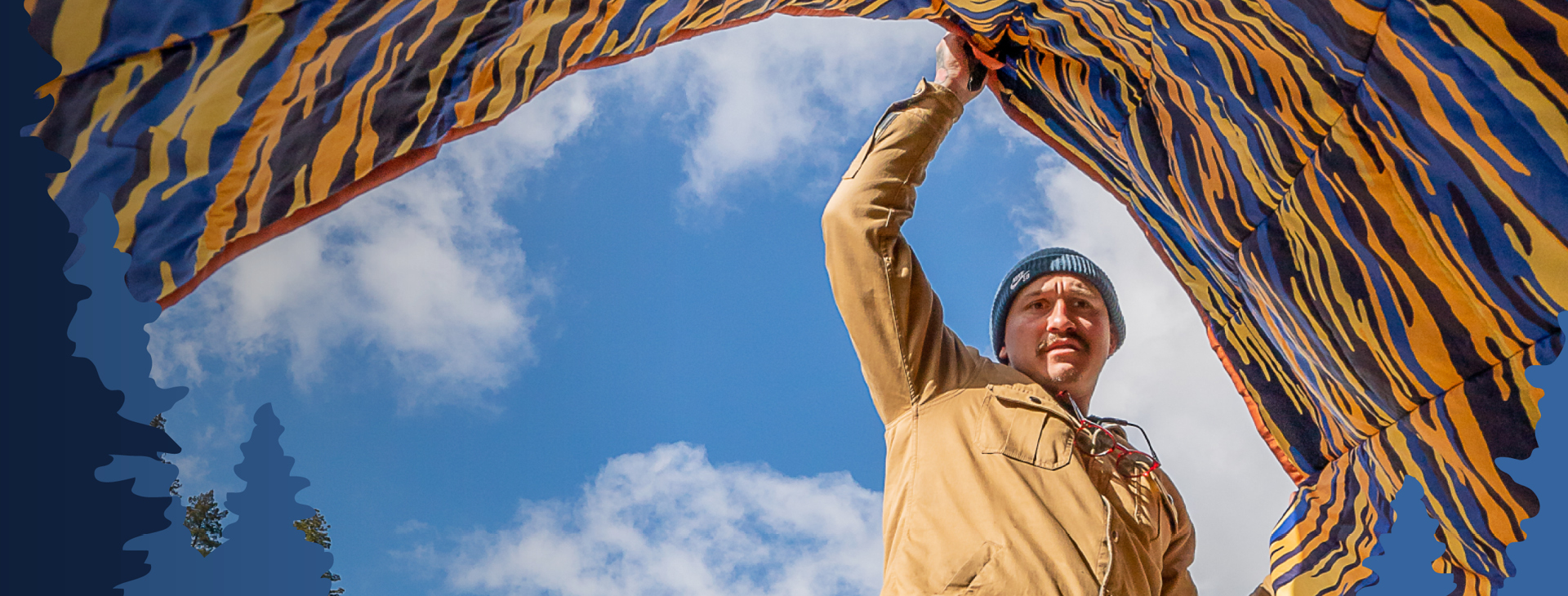Man with blue and orange blanket, with blue sky in the background.