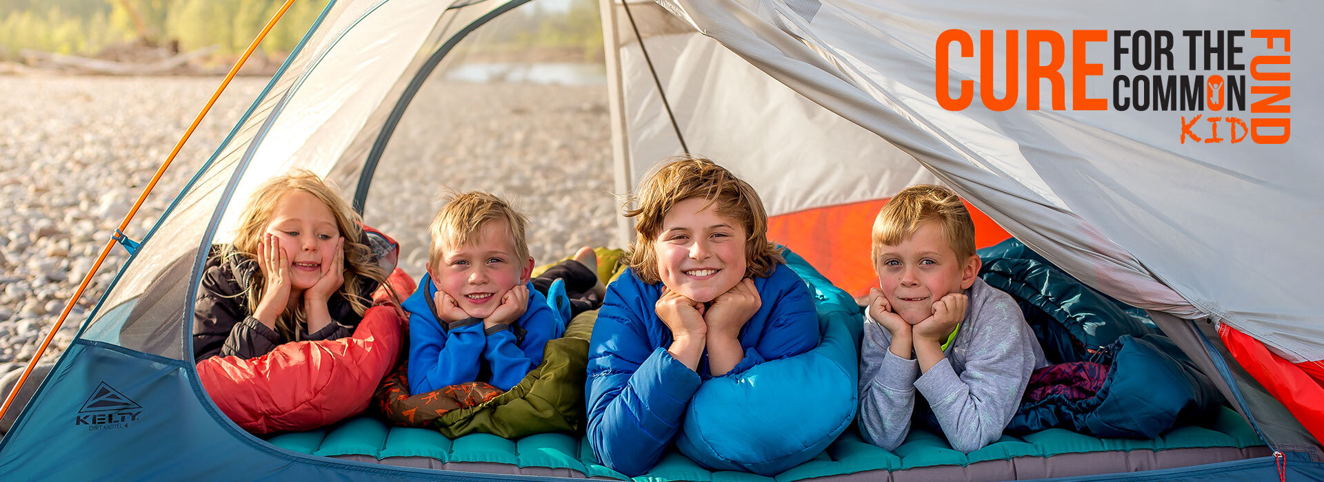 Kids in a kelty tent facing the camera