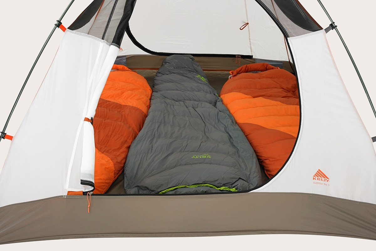 Close up of the Kelty Outfitter Pro 3 person tent, showing front door unzipped, rolled up, and secured with a toggle to the tent body