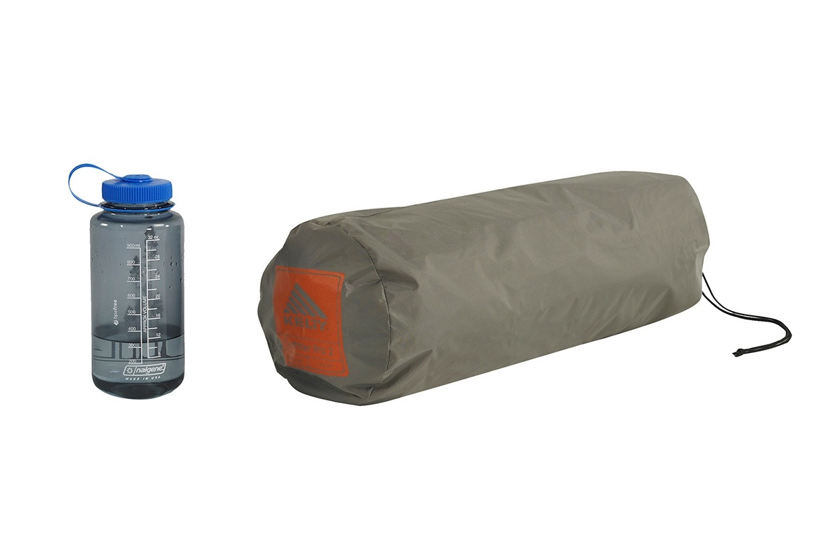 Kelty Outfitter Pro 2 person tent, packed inside a tan cylinder-shaped storage bag, shown next to a 32 oz. water bottle