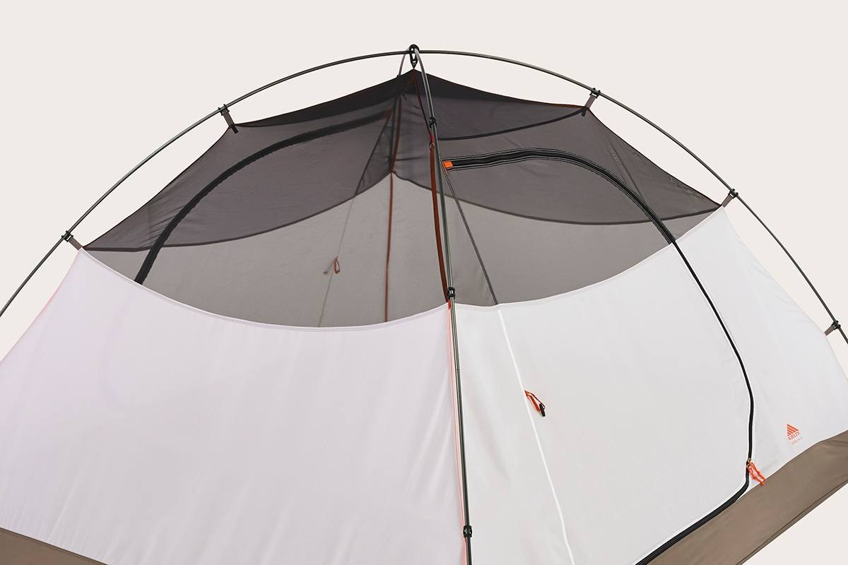 Close up of the top of Kelty Outfitter Pro 4 person tent, showing grey mesh at the top of the tent body, and two tent poles attached with color-coded plastic clips