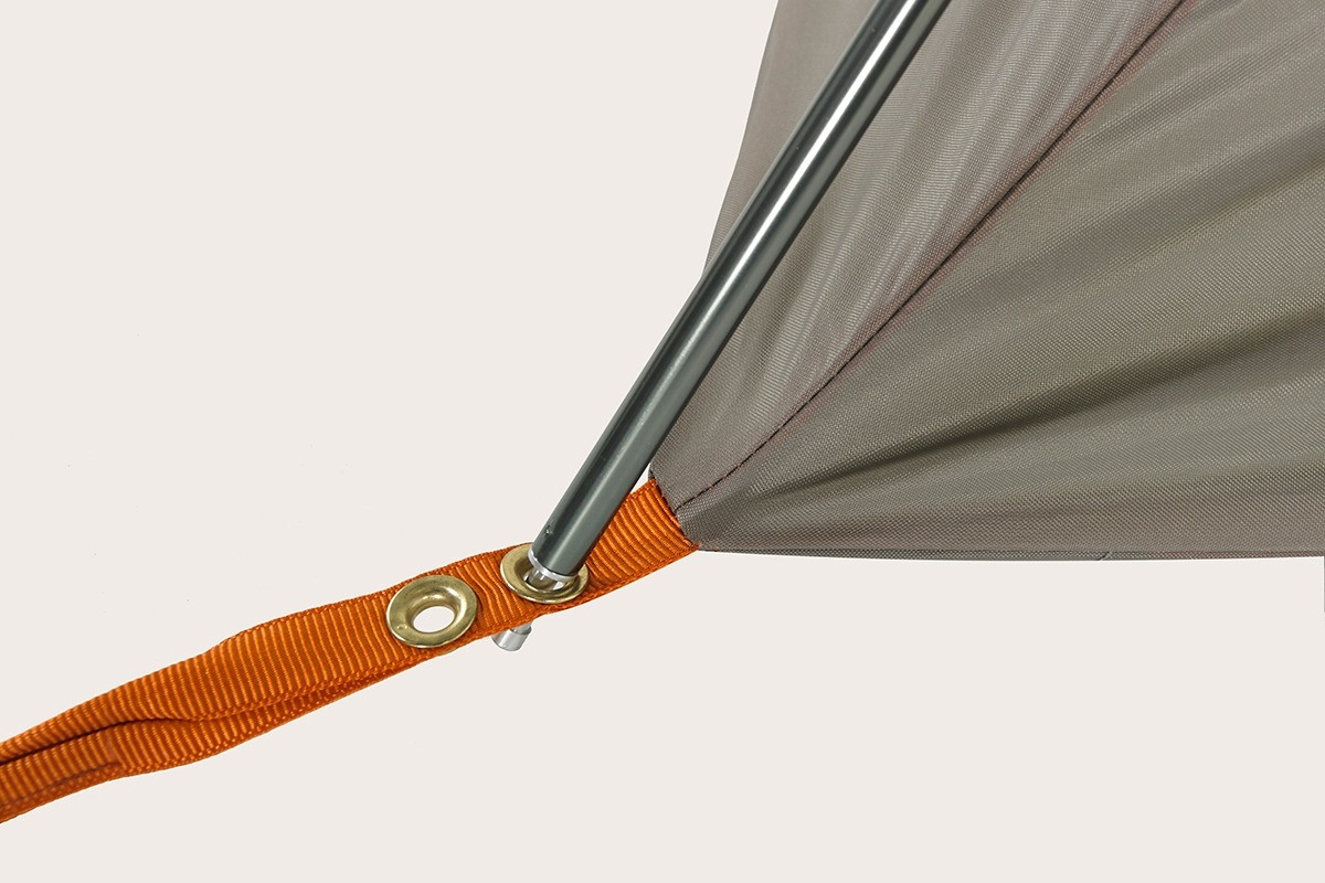 Close up of the Kelty Outfitter Pro 4 person tent, showing tent pole inserted into a metal grommet at the bottom corner of tent