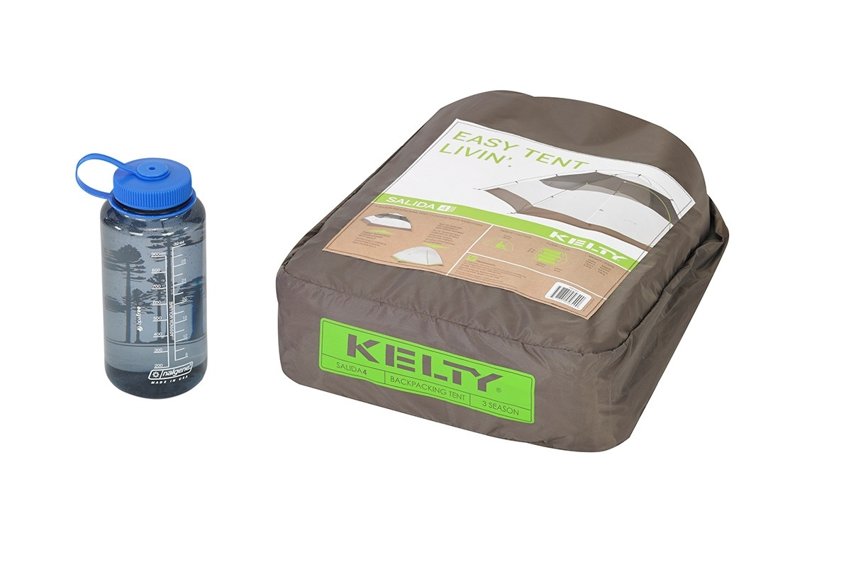 Kelty Salida 4 person tent, shown packed inside tan square-shaped storage bag, next to 32 oz. water bottle