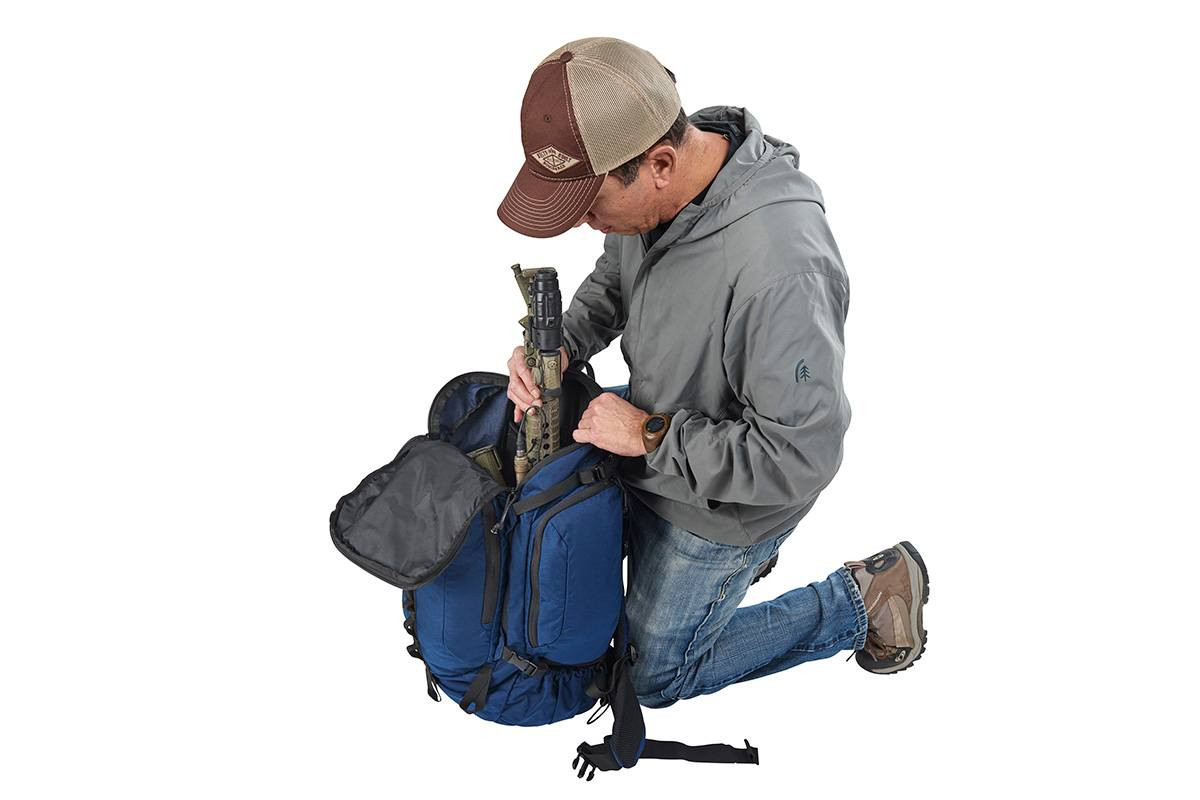 Man kneeling beside Kelty Redwing 50 USA backpack, putting gear inside the pack