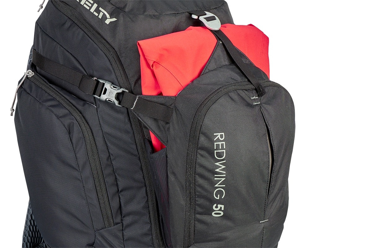 Close up of Kelty Redwing 50 backpack, showing red jacket packed in front pocket