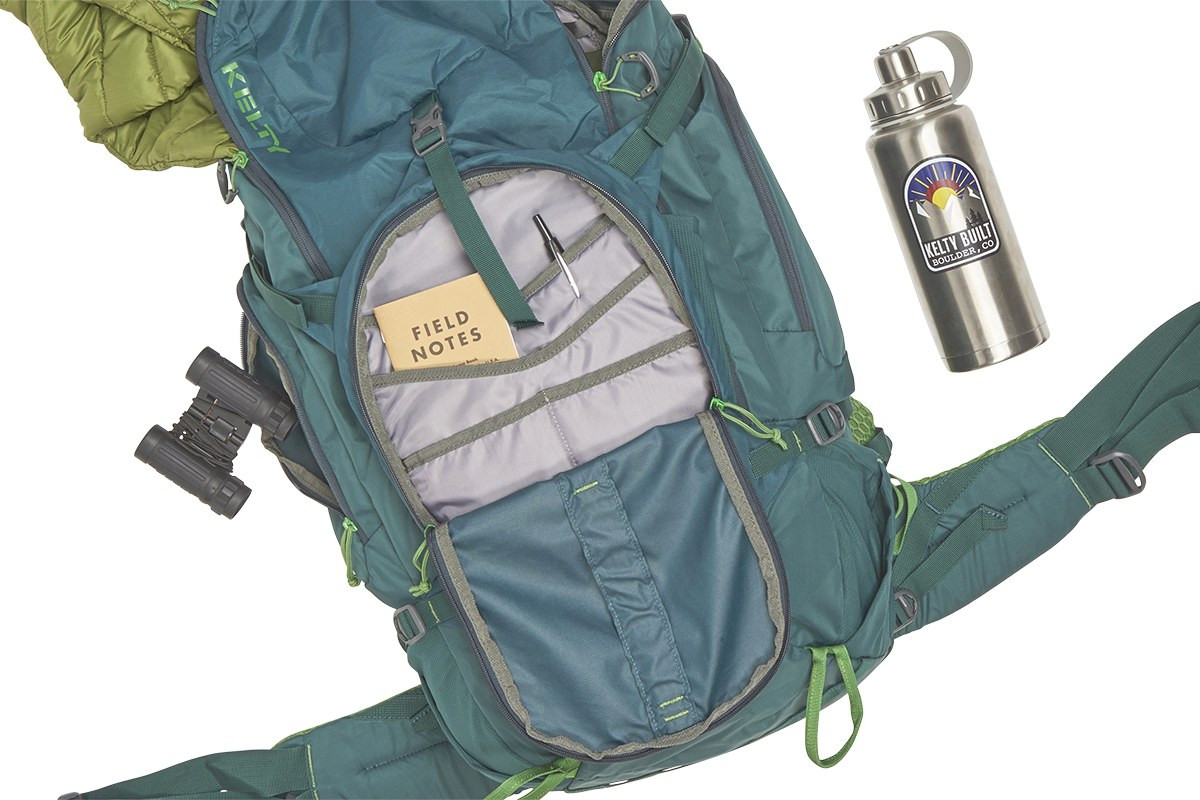 Top view of Kelty Redwing 44 backpack, unzipped, with binoculars, insulated jacket, water bottle, and notebook