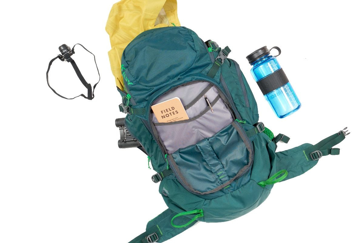 Top view of Kelty Redwing 32 backpack, unzipped, with binoculars, headlamp, rain jacket, water bottle, and notebook