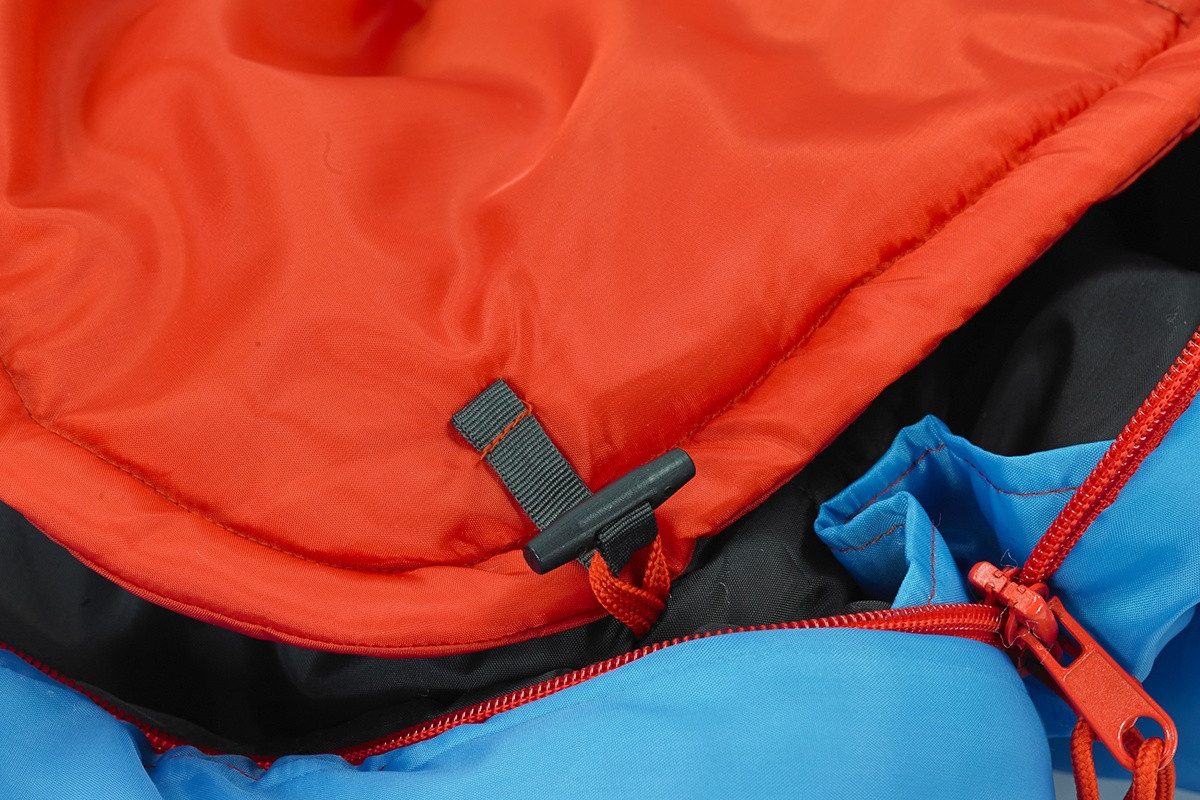 Close up of Kelty Tru.Comfort Kids 35, Paradise Blue, showing how blanket attaches to the body of bag with a plastic toggle