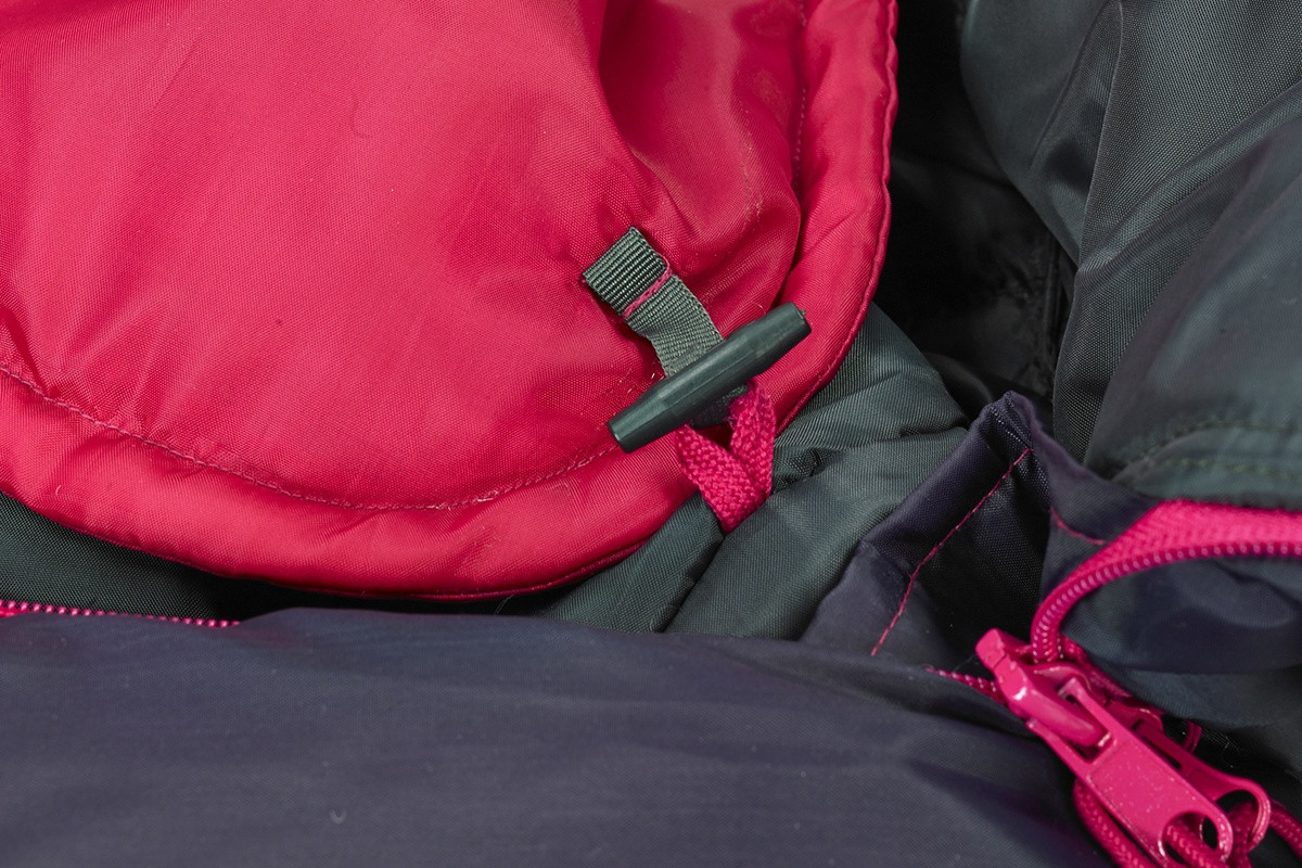 Close up of Kelty Tru.Comfort Kids 35, Black Cherry, showing how blanket attaches to the body of bag with a plastic toggle