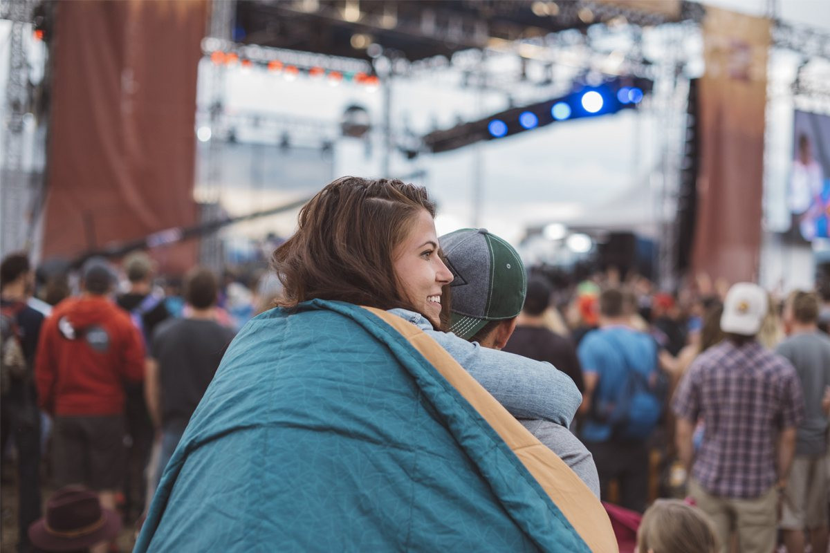 Woman with Kelty Bestie Blanket at a summer music concert