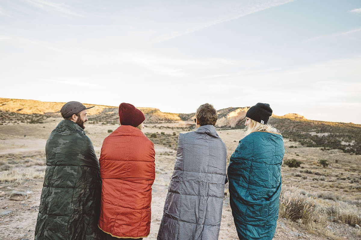 Group of four friends on a camping trip, wearing Kelty Bestie Blankets in various colors