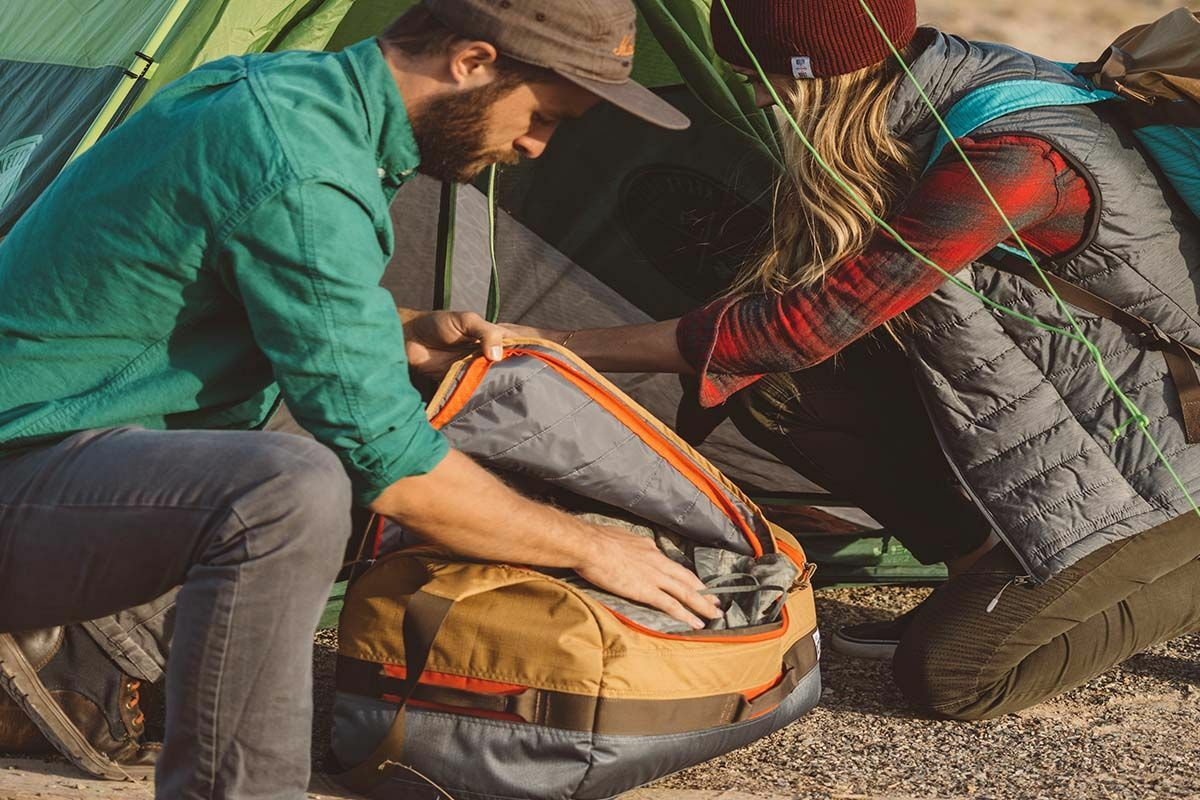 Couple with Kelty Dodger Duffel bag next to tent