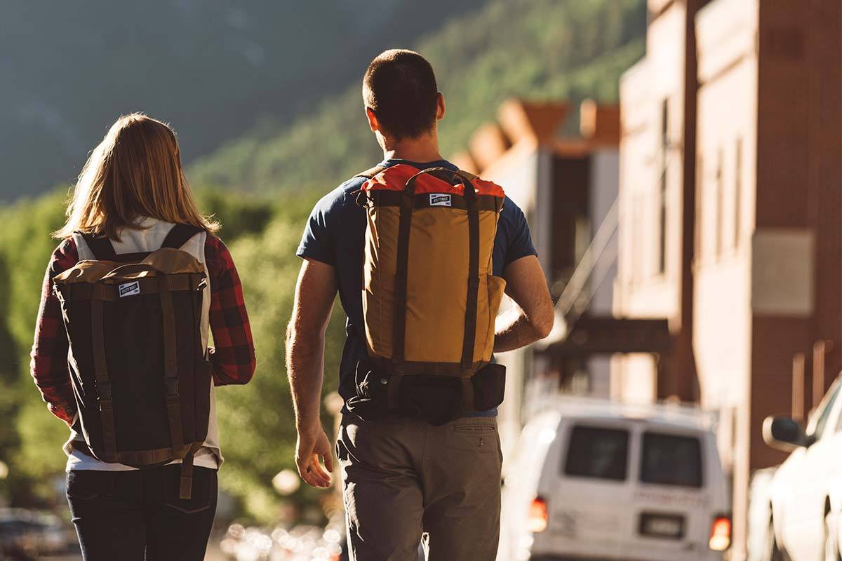 Couple wearing Kelty Hyphen Pack-Totes while walking down the street of a small mountain town