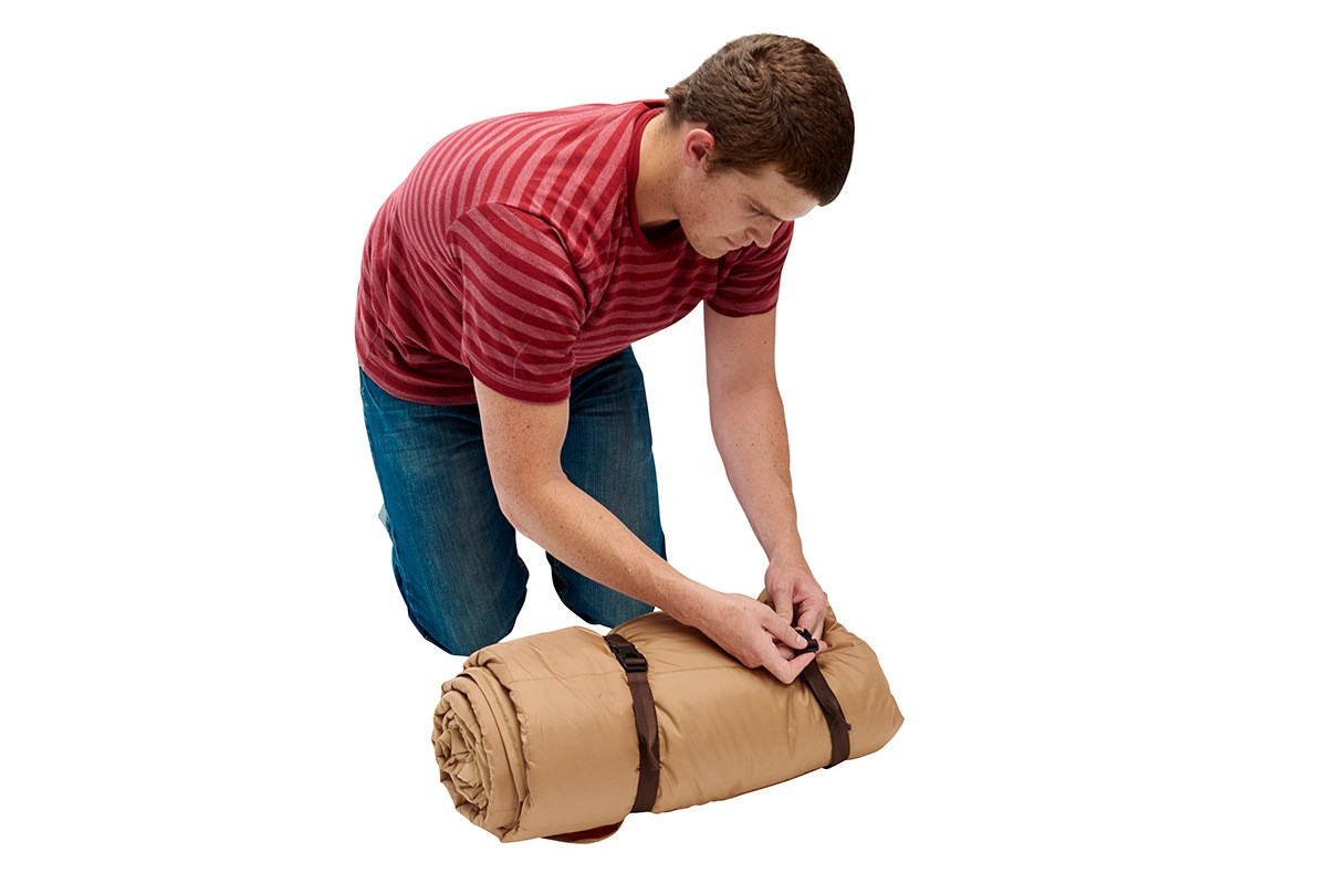 Man securing rolled-up Kelty Shindig Blanket with brown nylon straps