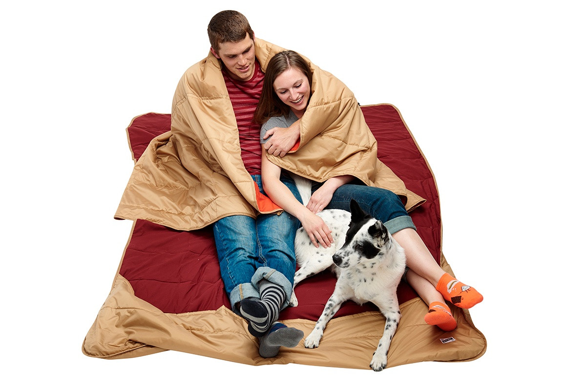 Man and woman sitting on Kelty Shindig Blanket with a dog