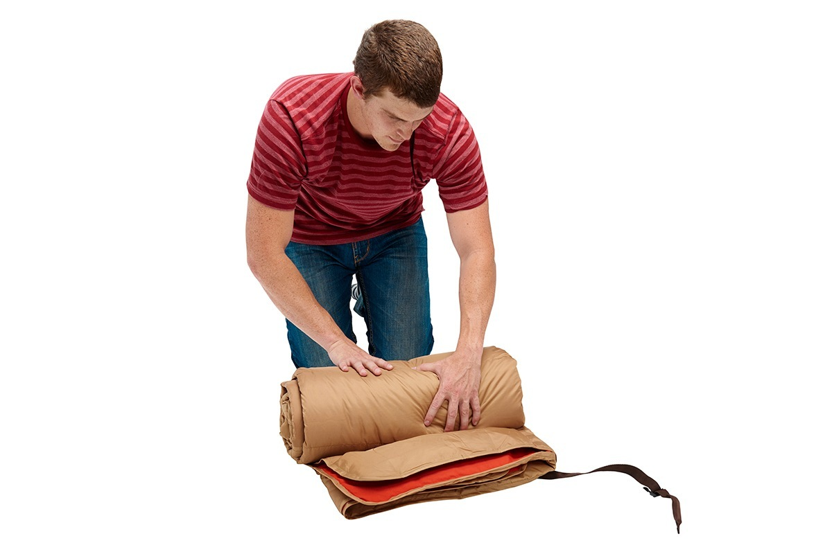 Man rolling up Kelty Shindig Blanket