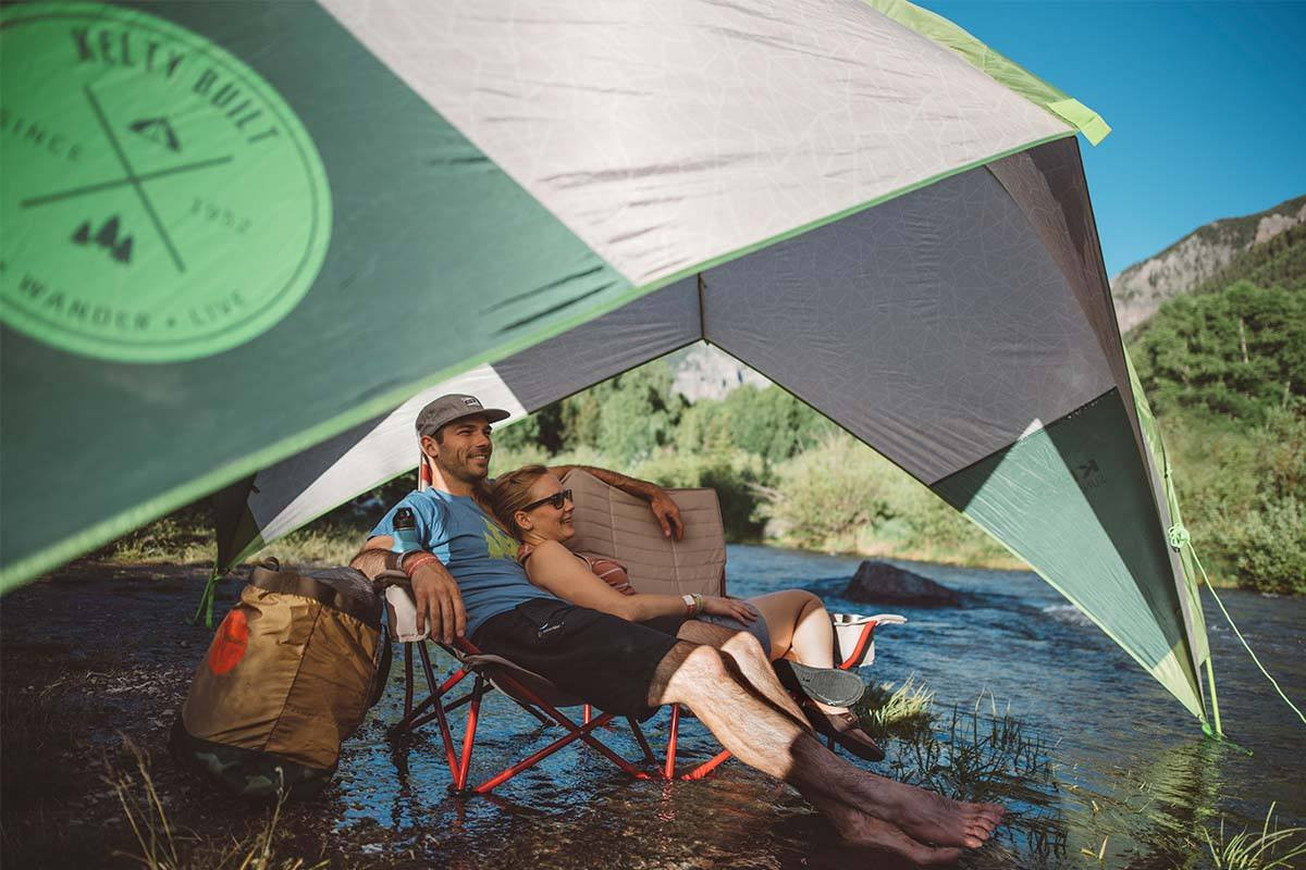 Couple sitting under Kelty Sunshade With Side Wall in a stream