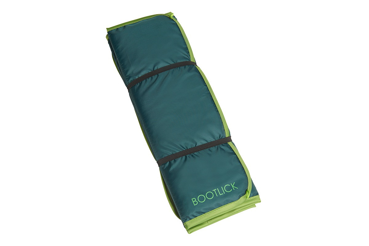 Kelty Bootlick doormat, green colorway, folded and secured with black elastic straps