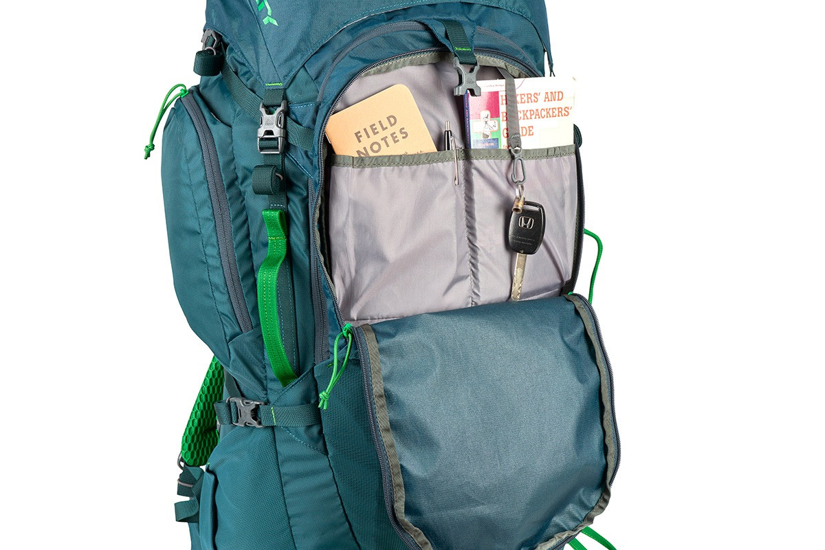 Close up of Kelty Coyote 65 backpack, Ponderosa Pine, with front compartment unzipped, showing multiple storage pockets