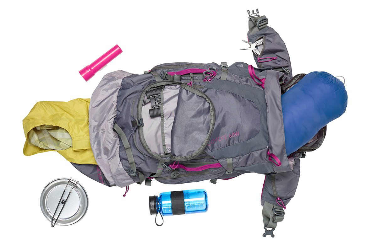 Top view of Kelty Women's Coyote 60 backpack, with bag unzipped and a variety of camping gear next to the pack