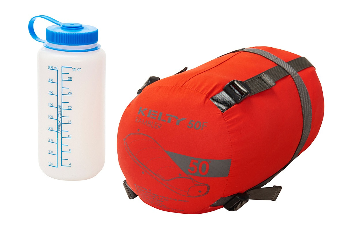Kelty Rambler 50 sleeping bag packed inside orange cylinder-shaped storage bag, shown next to 32 oz. water bottle