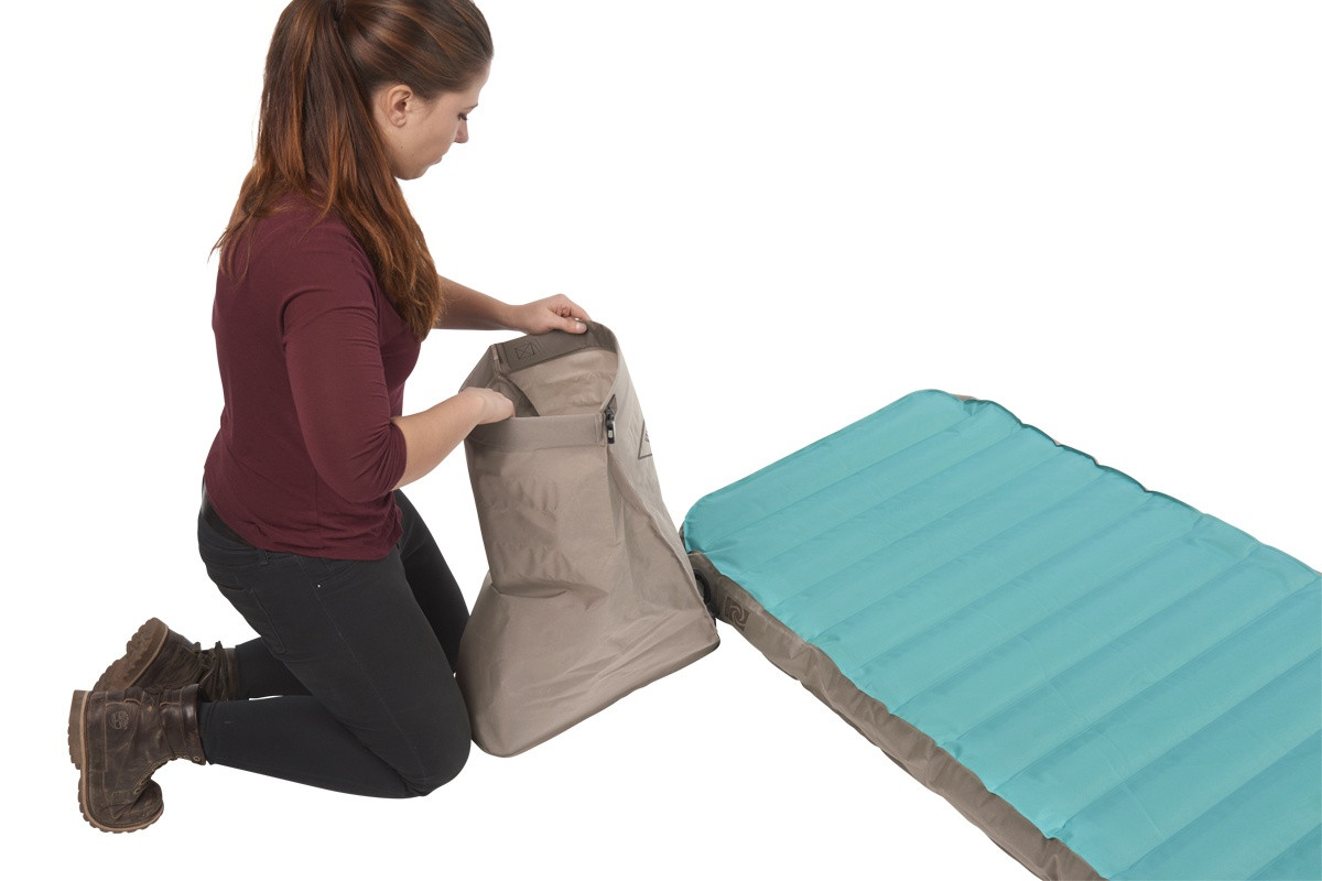 Woman closing the top flap of the Kelty Tru.Comfort Camp Bed Single pump bag