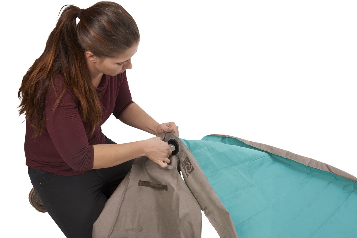 Woman attaching pump bag to Kelty Tru.Comfort Camp Bed Single