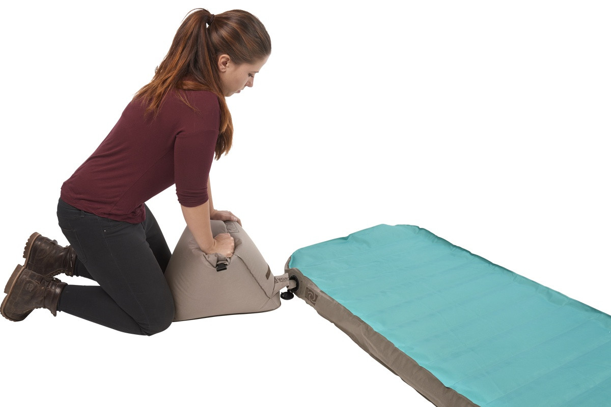 Woman inflating the Kelty Tru.Comfort Camp Bed Single with pump bag