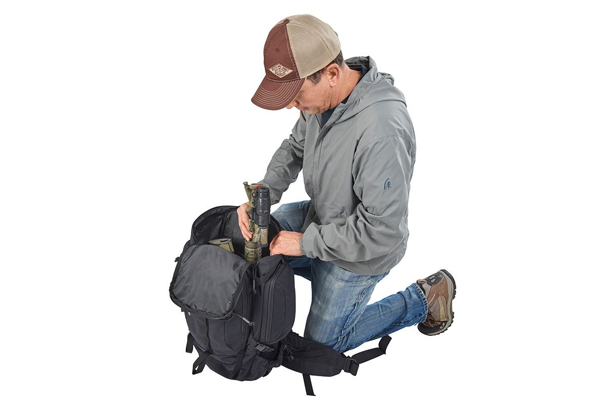 Man kneeling beside Kelty Redwing 44 Tactical backpack, packing gear into the main compartment of pack