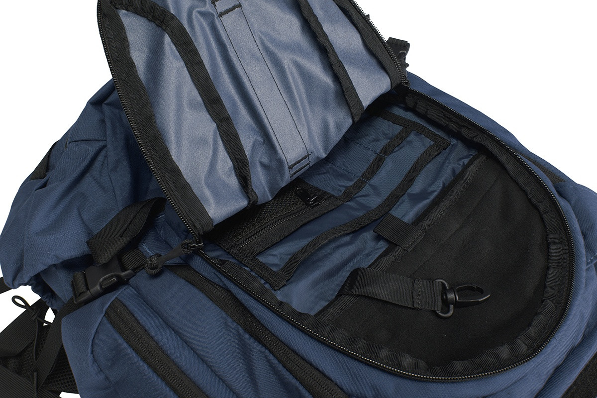 Close up of Kelty Redwing 44 Tactical backpack, with front pocket unzipped to show multiple smaller storage pockets inside