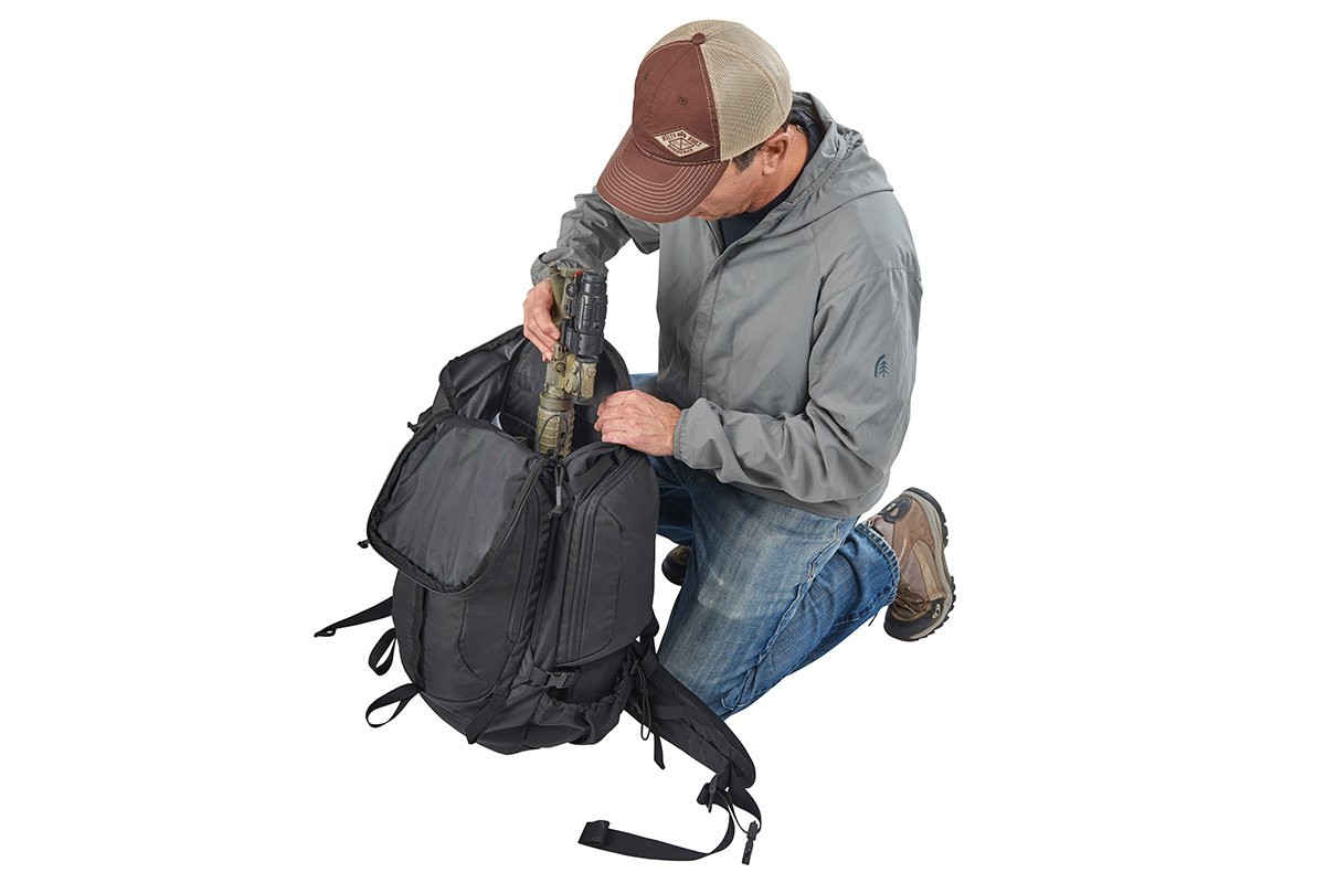 Man kneeling beside Kelty Redwing 50 Tactical backpack, putting gear inside the pack